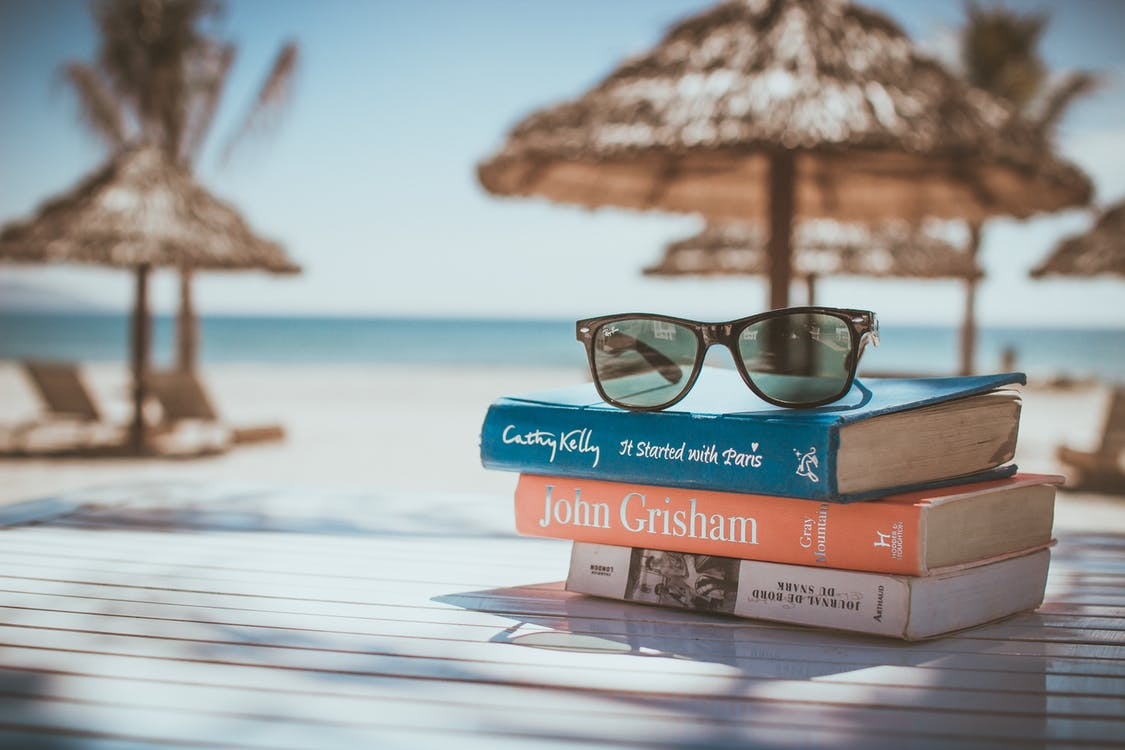 Grey Wayfarer-style Sunglasses on Top of Books on Top of Table