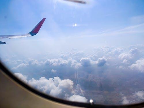 Ilmainen kuvapankkikuva tunnisteilla lentokoneen ikkuna, lentokoneen siipi, matkamuistoja, pilvet