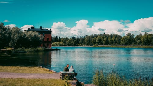 Man and Woman Sitting on Bench Near Body of Water