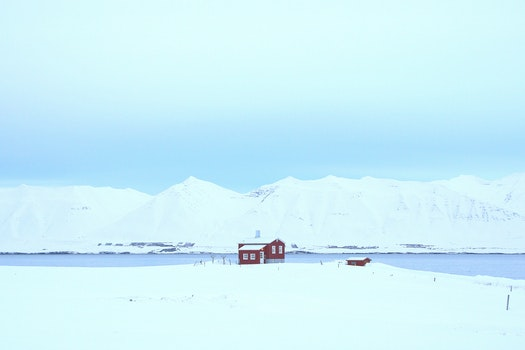 Red Bungalow on Snow Covered Field Surrounded by Large Body of Water