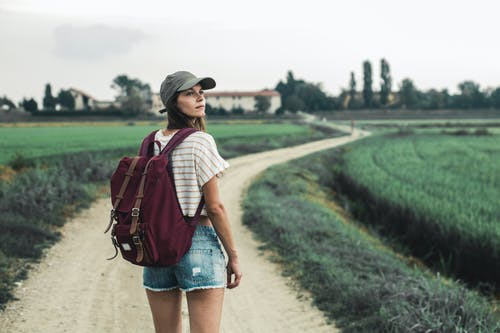 Woman in White and Red Stripe Shirt and Blue Denim Shorts Carrying Red Leather Backpack Walking