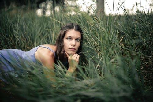 Woman in White Tank Top on Green Grass Field