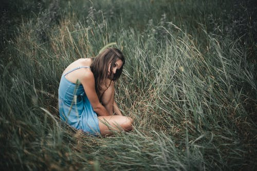 Woman in Blue Tank Top Sitting on Brown Grass Field