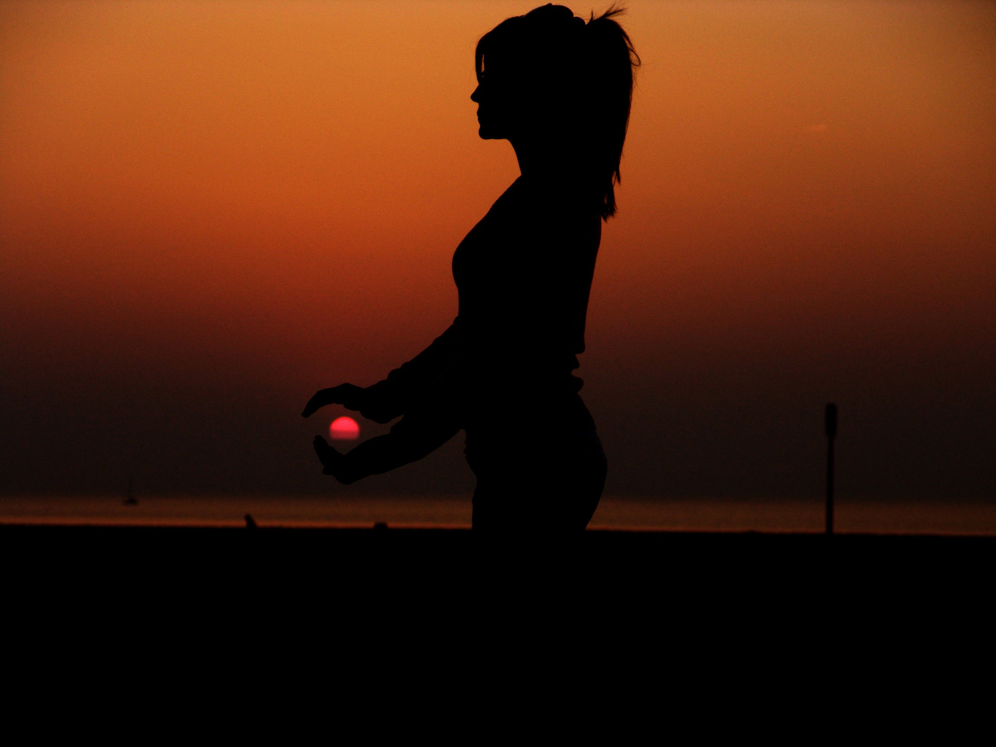 Force Perspective Photography of a Silhouette of a Woman Holding the Sun