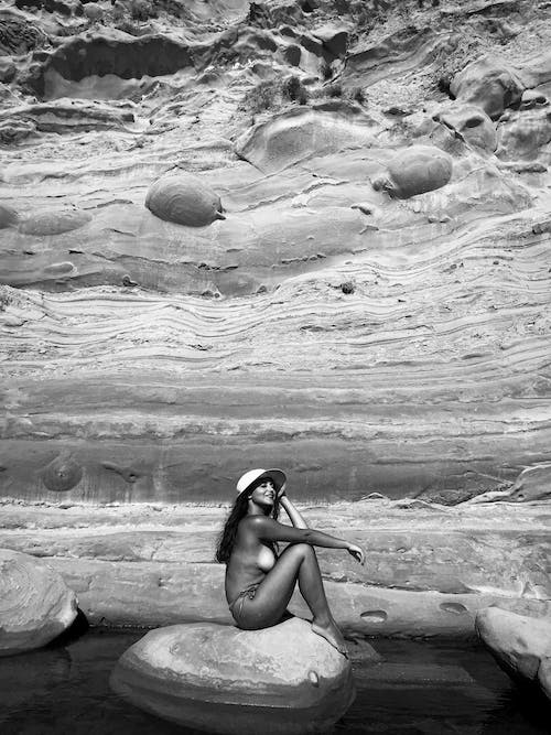 Topless woman sitting on stone