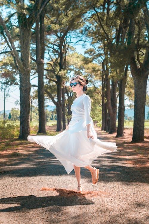 Woman in White Dress Walking on Pathway Between Trees