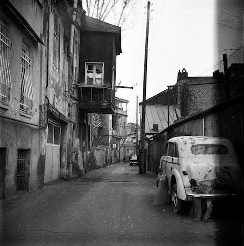 Abandoned car on old shabby street