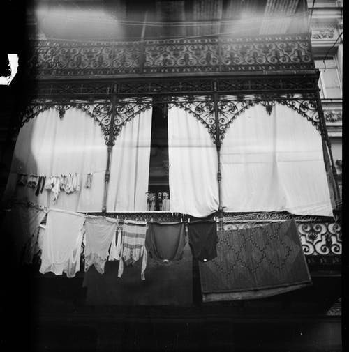 Black and white of film photo of old construction and metal balcony with garment on clothesline