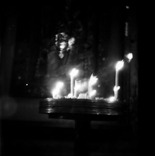 Black and white of film shot of flaming candles in coaster in front of icon