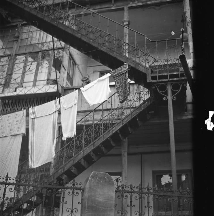 Black and white of metal stairway with railings near classic building and clothesline with towels