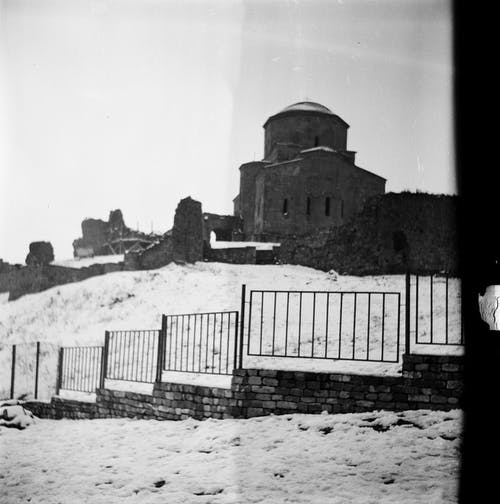 Black and white of classic construction with dome and windows behind metal fence in winter