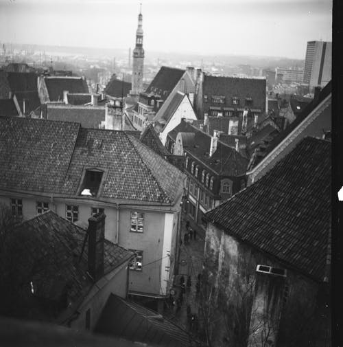 Black and white of aged houses with shabby roofs and tower in city