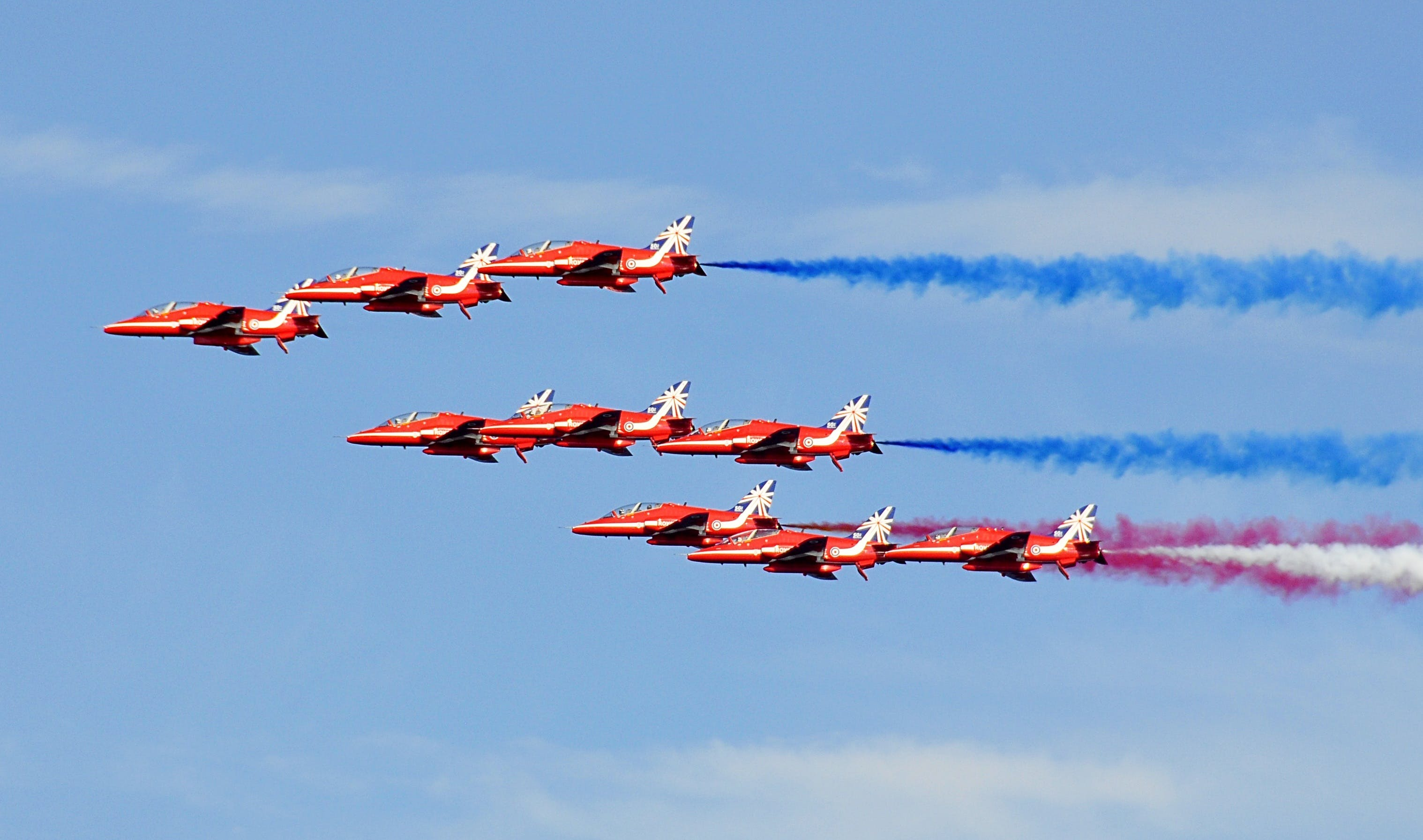 Red Jet Fighter Planes With Assorted Colors of Smoke on Horizon