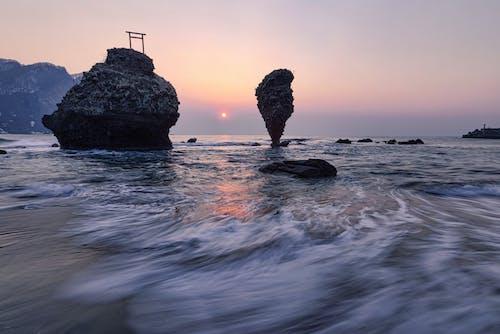 Cliffs in sea near coast at sunset