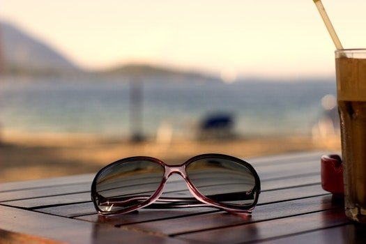 Pink Plastic Framed Wayfarer Sunglasses on Brown Table Top