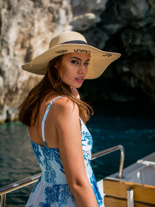 Woman in Blue and White Floral Spaghetti Strap Dress Wearing Brown Sun Hat