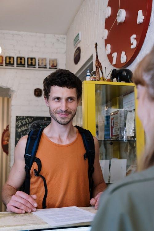 Man in Orange Crew Neck T-shirt Smiling