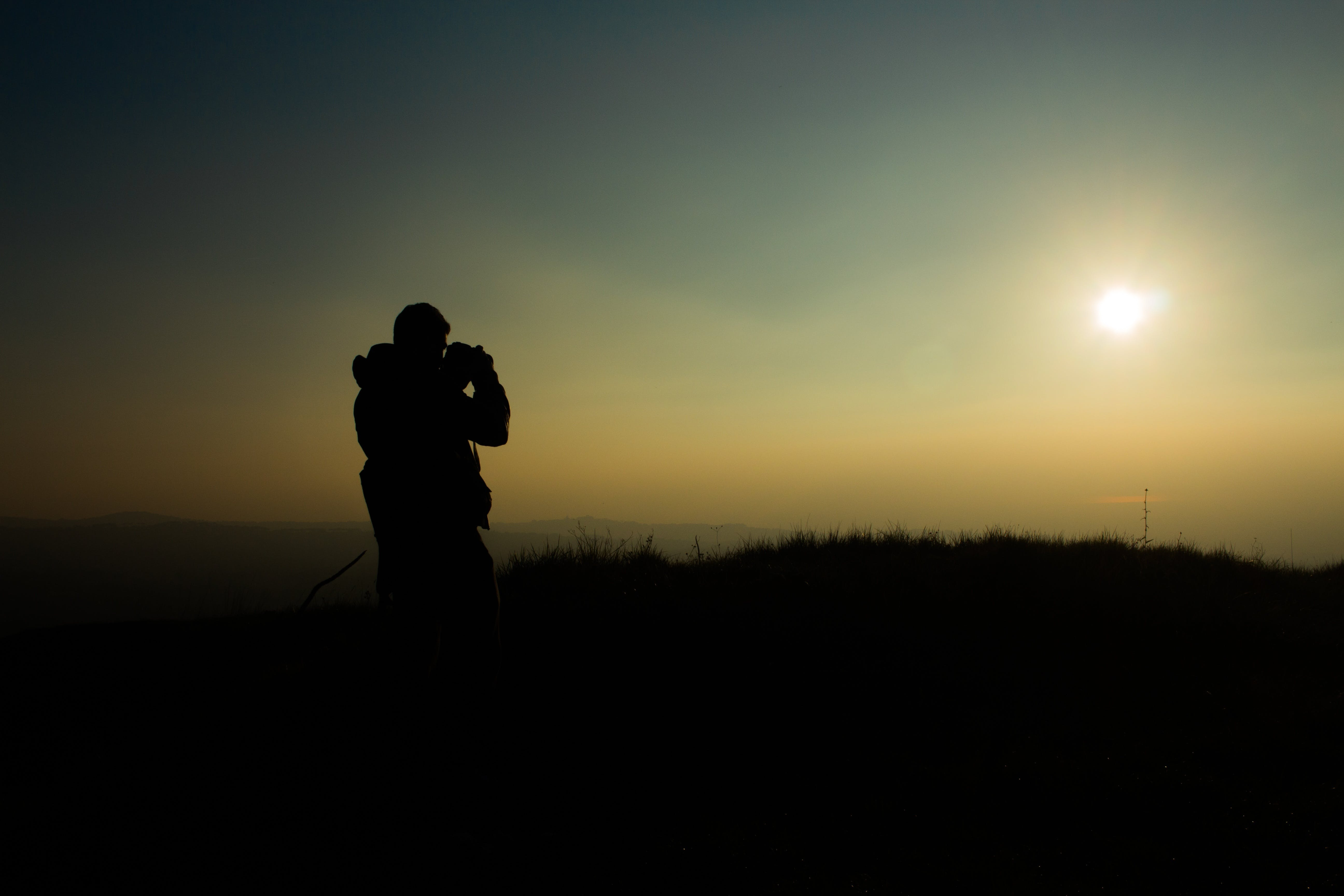 Silhouette of Man Holding Camera in Sunset