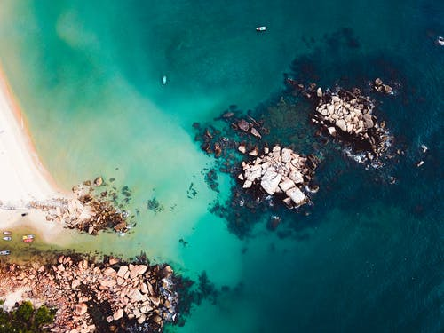Aerial view of turquoise water washing sandy beach and rocky island in bright day