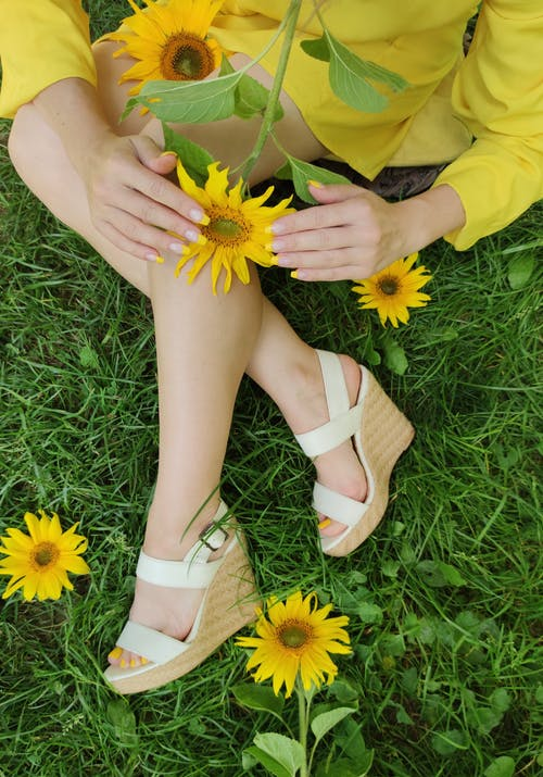 Woman in White Peep Toe Sandals Holding Yellow Flower