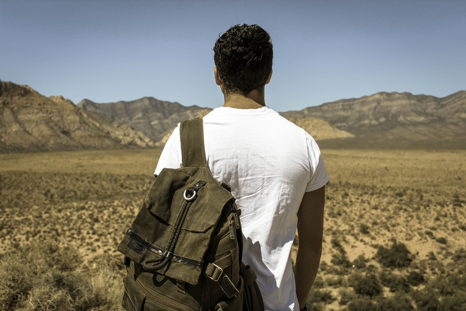 Man Wearing White Crew Neck T-shirt and Gray Backpack Standing by the Desert during Daytime