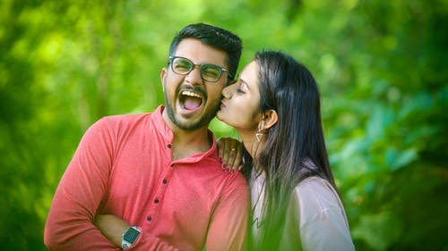 Positive Indian woman kissing cheerful smiling man in glasses on blurred background of bright greenery