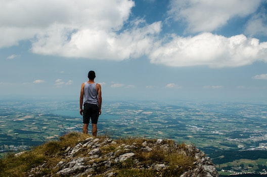 Man on Gray Sleeveless Shirt Standing on the Edge of Mountain