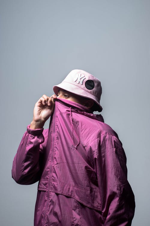 Stylish young guy covering face with jacket