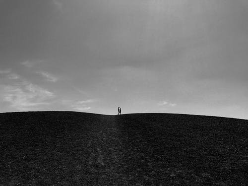 Grayscale Photo of Person Standing on Hill