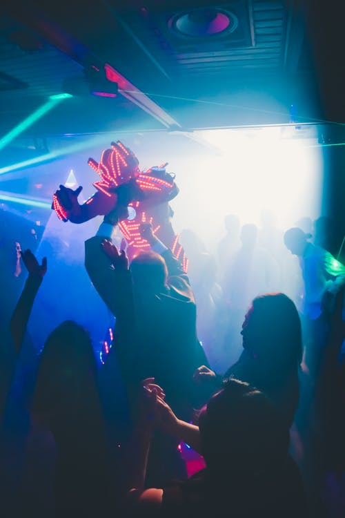 Silhouettes of unrecognizable people dancing in nightclub near person in costume with neon lights
