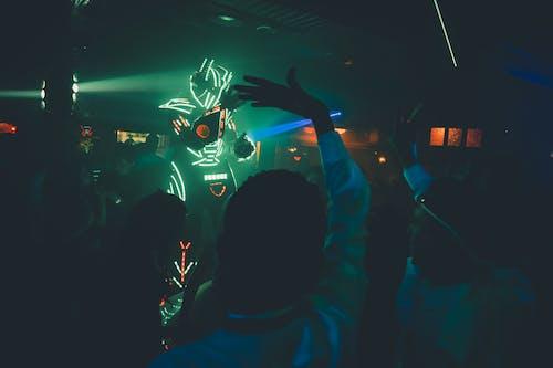 Unrecognizable person in futuristic costume with neon lights making show in dark nightclub near dancing people