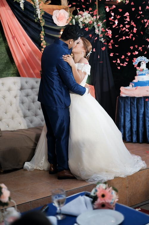 Man in Black Suit Kissing Woman in White Wedding Dress