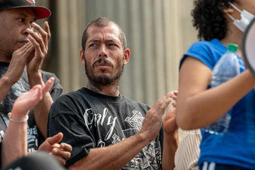 Serious bearded man in casual clothes standing on street with unrecognizable multiracial people and applauding during protests against racial discrimination