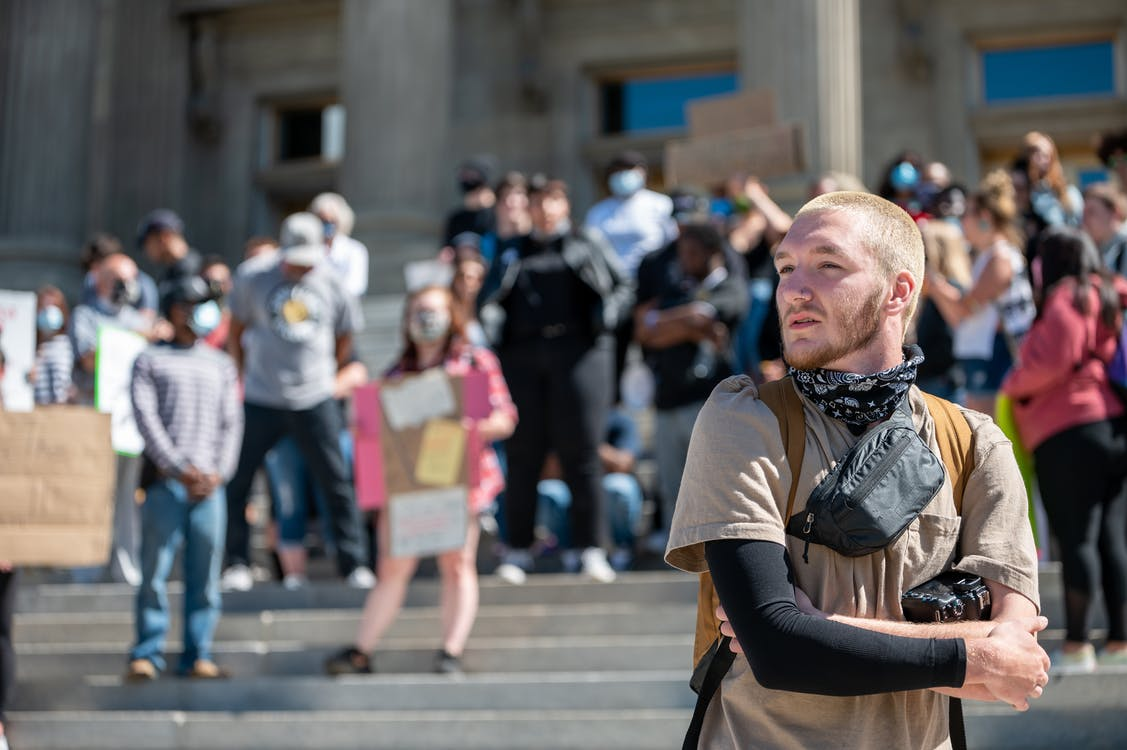 Pensive young bearded guy in casual clothes and backpack standing on street with group of protesting people and looking away during BLM demonstration