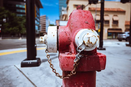 Typical red fire hydrant with rusty chain located on roadside in modern city on sunny day