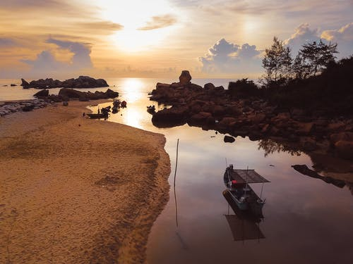Picturesque view of colorful sunset sky over calm sea with sandy coast and small boat