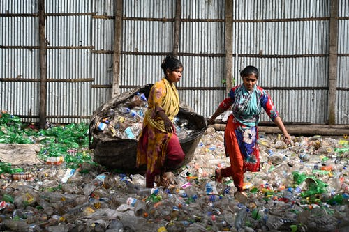 Women Pulling a Bag of Recycled Trash