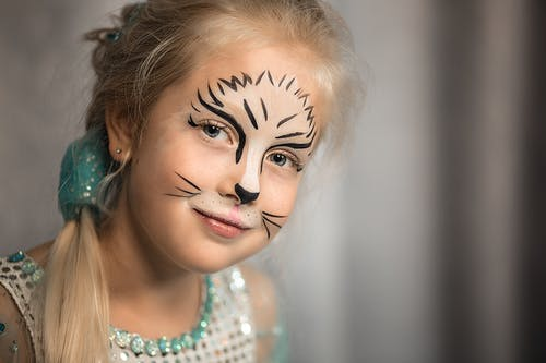 Happy blond haired child with braid and painted face on party looking at camera