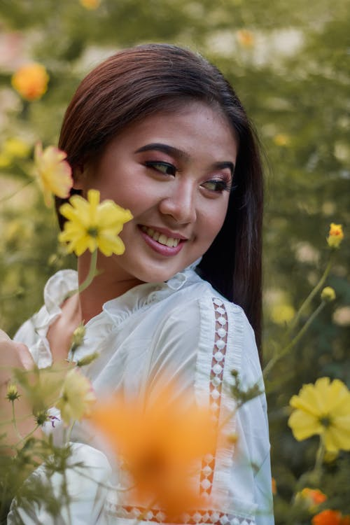 Delighted young Asian lady recreating in garden among delicate flowers