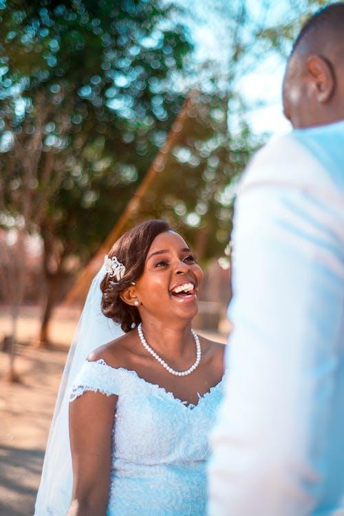 Happy black bride in wedding dress with groom at wedding