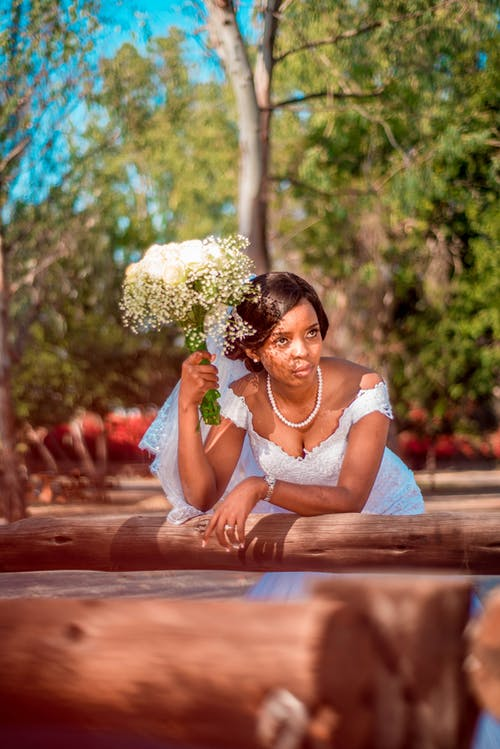 Pensive young African American bride in elegant wedding dress with bouquet of white flowers thinking on question