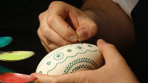 Person Holding Oval White and Green Ornament