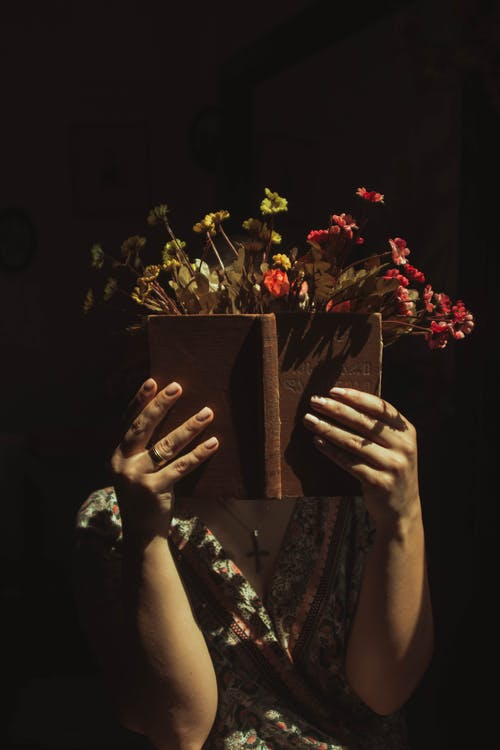 Woman opening book decorated with flowers