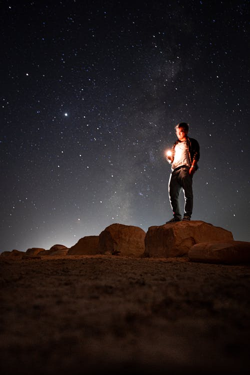 Full body of male standing on stone with hand in pocket and bright light in hand against starry sky in darkness