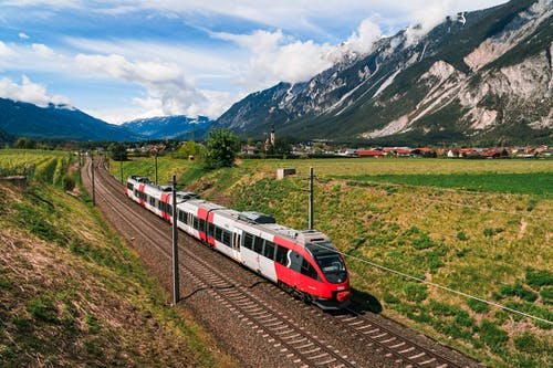 Red and White Train on Rail Road Near Green Grass Field and Mountains