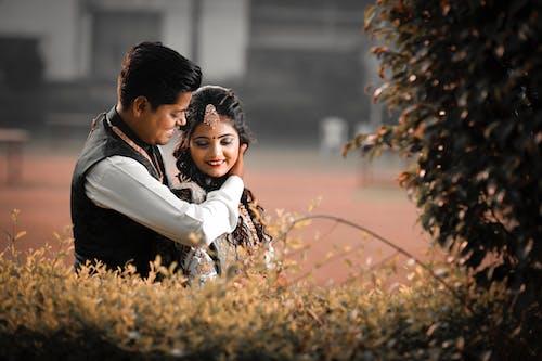 Loving ethnic couple near green shrub
