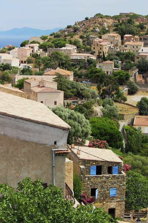From above of town with typical houses located on hill with green vegetation against cloudless sky in nature in daytime