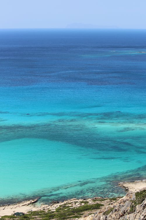 From above of azure calm ocean near stony shore against blue sky line on horizon in summer day in tropical resort