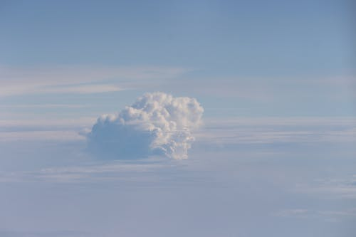 White fluffy cumulus cloud floating against skyline on blue sky in daytime in nature outside