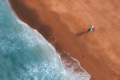 Sandy beach with colorful umbrella on sunny day